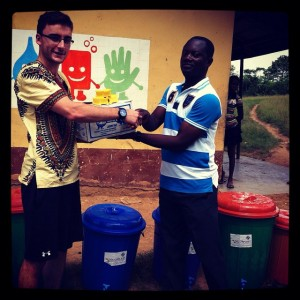 Patrick-presenting-soap-and-buckets-to-the-head-teacher-at-Amede-presby-school-to-boost-hand-washing