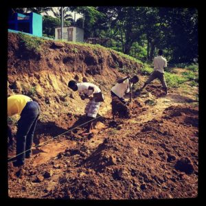 The-community-is-working-hard-to-help-build-the-retaining-wall-on-the-pitch-at-Abenta